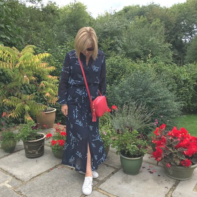 woman in navy shirt dress with red handbag
