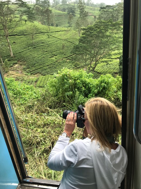 woman taking photo out of train door sri lanka