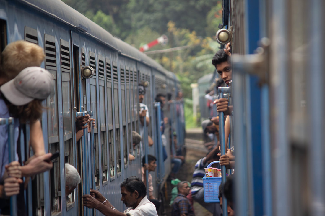 lots of people hanging out of trains in sri lanka