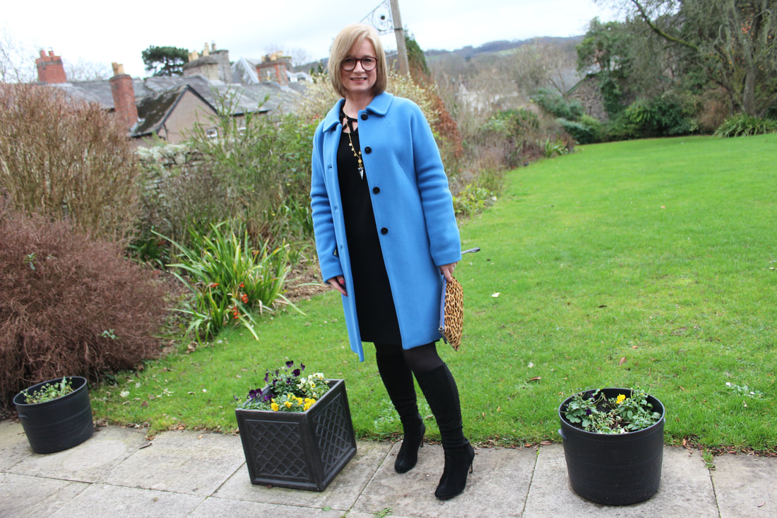 wearing a bright blue classic coat for a winter wedding