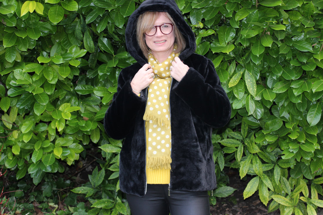 wearing black fur coat with bright yellow knit from Boden