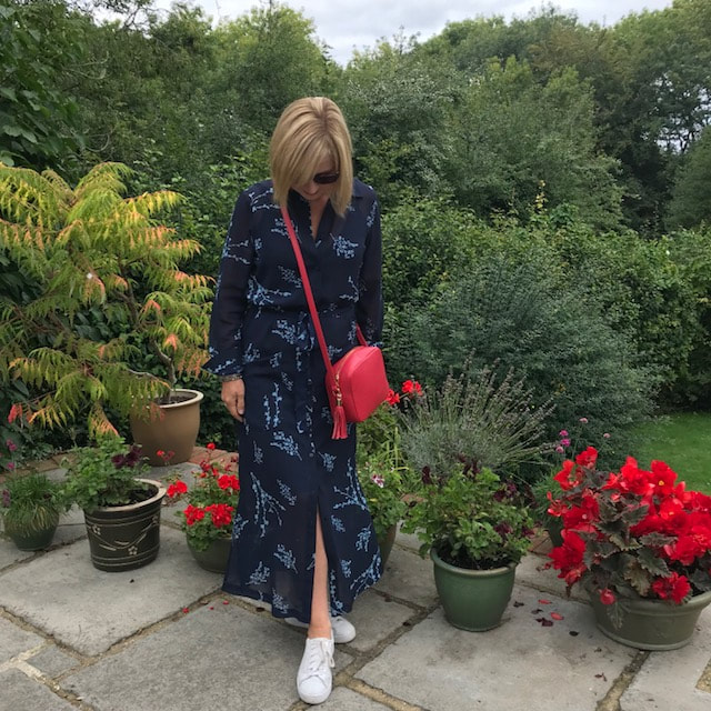 woman in garden with navy dress and red bag
