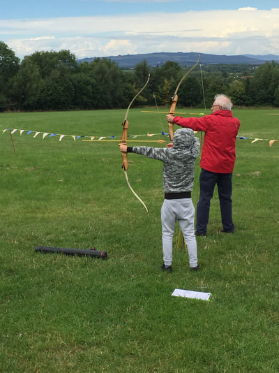 boy and grandfather archery