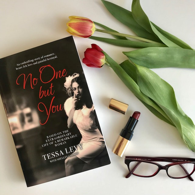 flat lay of book no one but you by tessa levy with lipstick and flower
